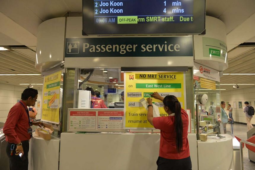 SMRT staff at Tiong Bahru station putting up signs to inform the public of the exercise.