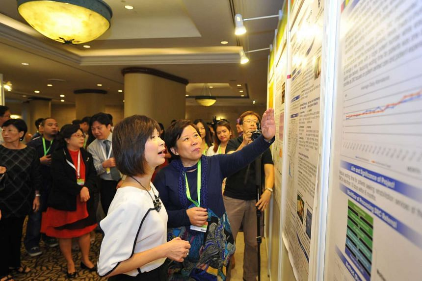 St Andrew's Community Hospital manager of inpatient therapy services Anna Lee (in black) showing Senior Minister of State for Health and the Environment and Water Resources Amy Khor to one of the winning abstracts by the hospital at the ILTC Quality