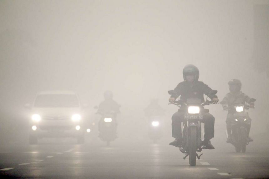 Motorists travelling under a heavy blanket of haze in Palangkaraya, capital of Central Kalimantan province, on Oct 12, 2015.