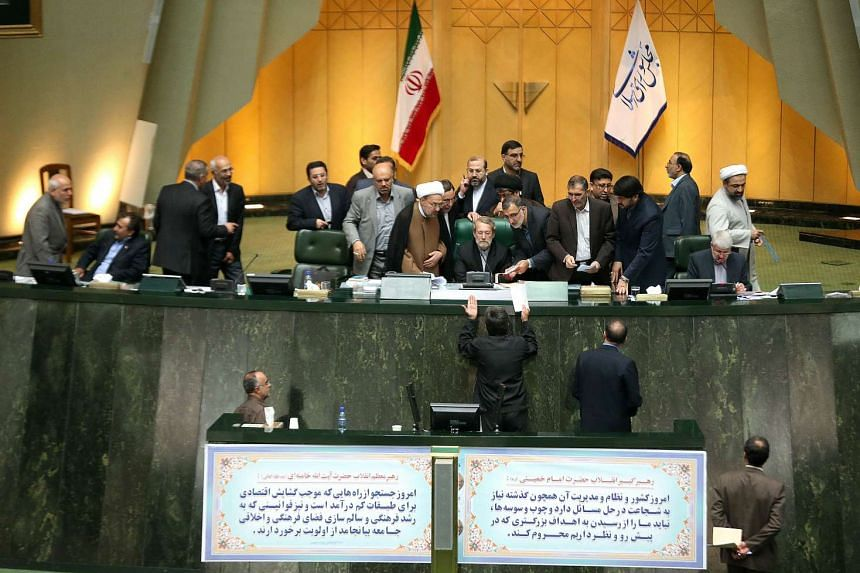 Iran's Parliament Speaker Ali Larijani (centre) listens to a deputy during a session in Teheran on Oct 13, 2015 in which the Islamic republic's parliament approved its nuclear deal with world powers.