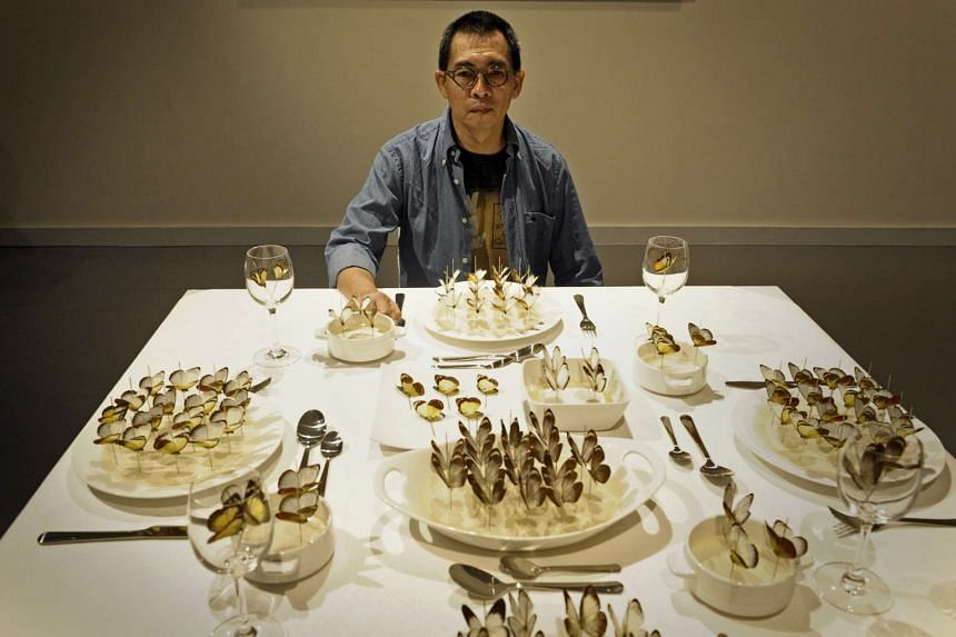 Indonesian visual artist FX Harsono poses with his 2008 installation, titled Bon Appetit, which is made up of dead butterflies on a dinner table.