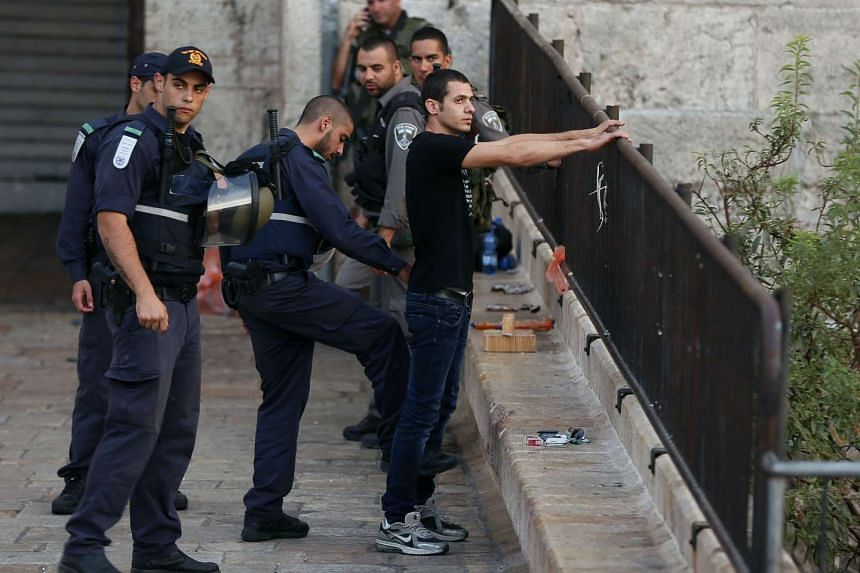 An Israeli policeman checking a Palestinian man at the entrance of the Old City in east Jerusalem on Oct 13.