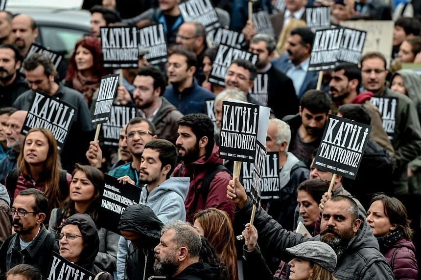 """Protesters hold placards that read """"We know the killer"""" as Turkish riot police block the road on Oct 13, 2015, in Istanbul."""