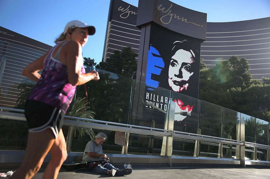 Michael McLean sets up to play his guitar for money near a billboard showing a picture of Democratic Presidential candidate Hillary Clinton advertising today's  Democratic Presidential debate at the Wynn Las Vegas resort and casino.