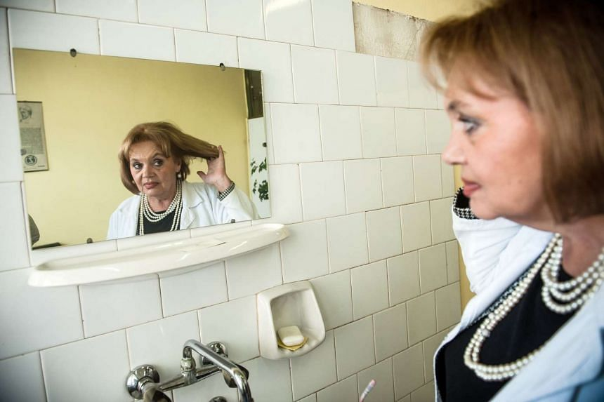 Serbian doctor Mirjana Stanojcic looks at herself in the mirror in Gornji Milanovac on Tuesday.
