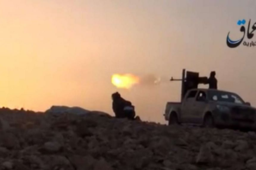This file image grab taken from a video uploaded by Aamaq News Agency, a Youtube channel which posts videos from areas under the ISIS group's control, allegedly shows Islamic State group fighters firing from an armed pick-up truck on the outskirts of