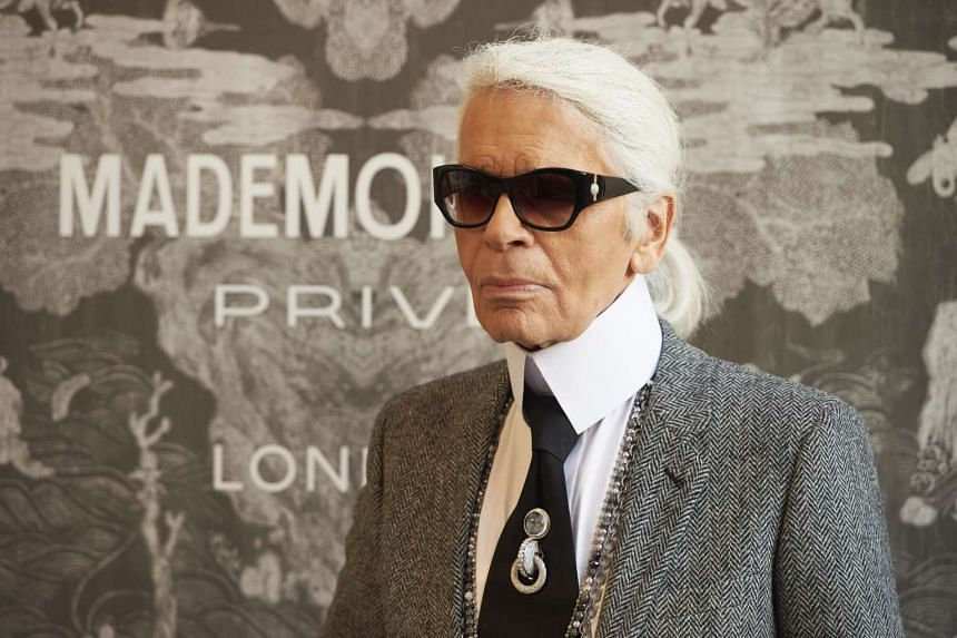 "German fashion designer Karl Lagerfeld, head designer and creative director of French fashion house Chanel, poses for a photograph as he arrives for a press-view of ""Mademoiselle Privé"" at the Saatchi Gallery in west London."