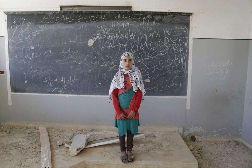 Malak, a 13-year-old girl, poses for a picture inside her damaged classroom at a school, which was used before as a military camp for forces loyal to Syria's President Bashar al-Assad, in the rebel-controlled town of Ain Qurei in the southern country