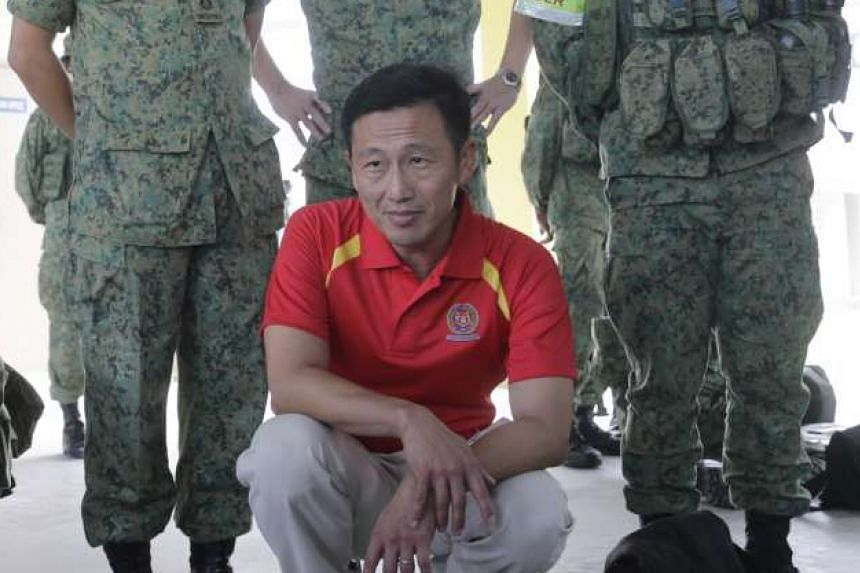 "Recruits gathering for a briefing during physical training at the Basic Military Training Centre in Pulau Tekong yesterday. Mr Ong (above) says there are ""synergies"" between his education and defence portfolios."