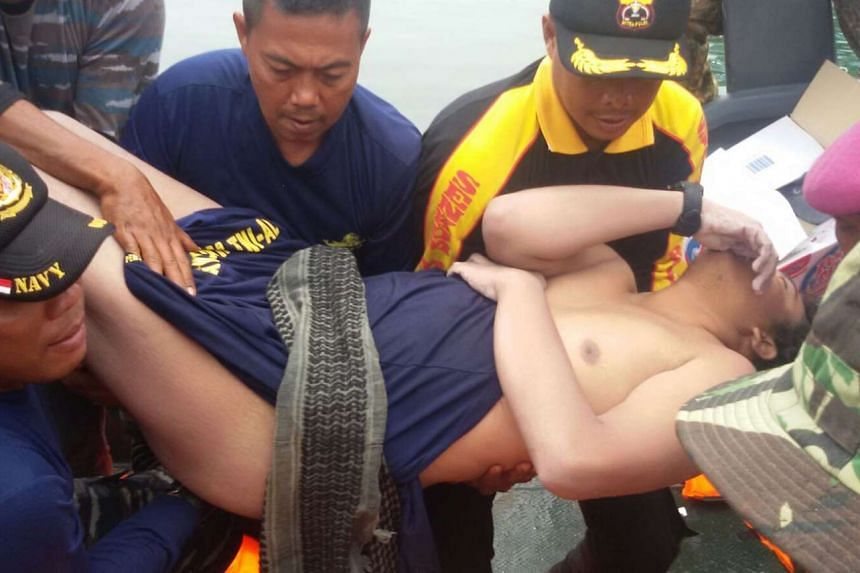Mr Fransiskus Subihardayan being carried by a rescue team from Sumatra's Lake Toba yesterday. Search teams are still hunting for the missing helicopter and the other passengers.
