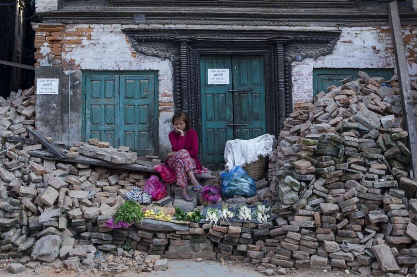 A Nepalese vendor waits for customers as she sits atop a pile of bricks collected from collapsed temples in Kathmandu. Since the April 25 earthquake in Nepal, which killed more than 8,000 people and displaced about three million, little has been done