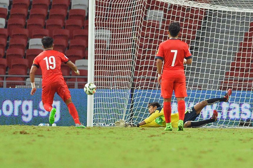 Cambodia's goalie ( above ) saves Khairul Amri's penalty. The striker is later stretchered off with a hamstring injury.