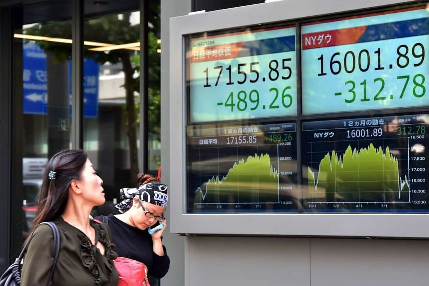 Pedestrians walking past a share price display in Tokyo on Sept 29.