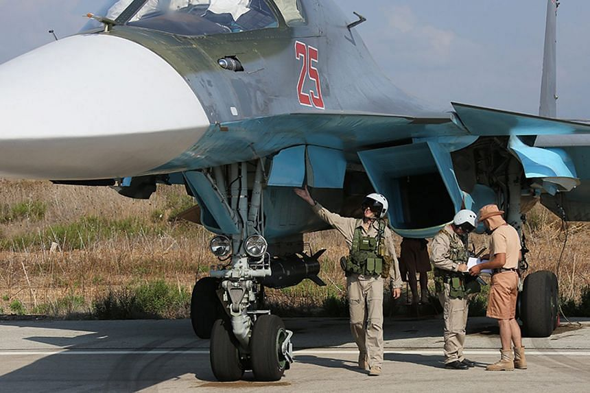 A photo dated Oct 3, 2015, shows Russian pilots checking their SU-34 bomber before a flight at the Syrian Hmeymim airbase.