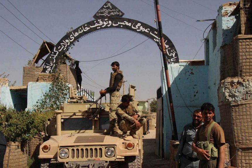 Security forces stand guard at the main gate of a prison in Kunduz, after retaking the Afghan city from the Taleban.