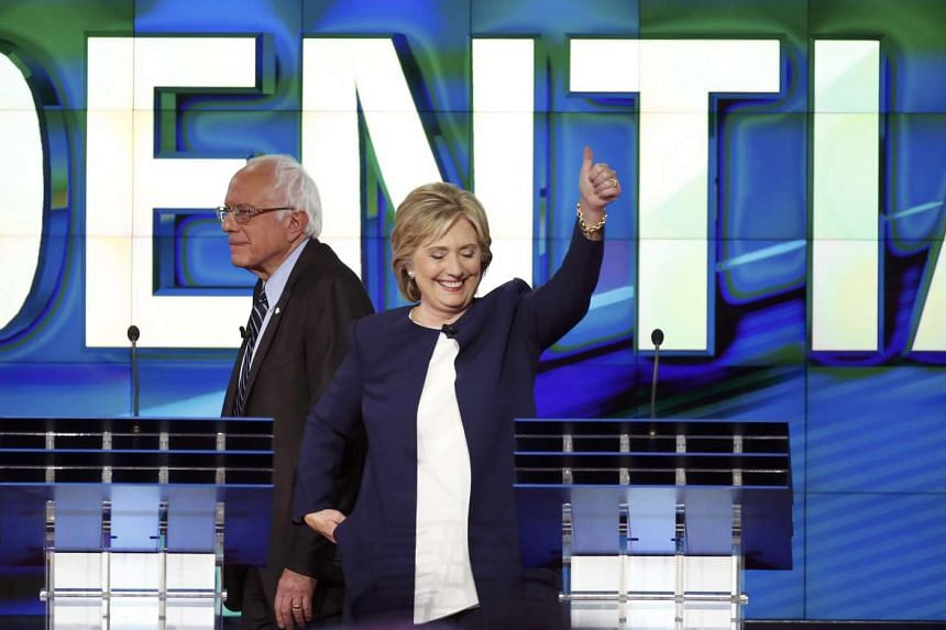 Democratic presidential candidate Hillary Clinton gives a thumbs up as she walks away from her podium as rival US Senator Bernie Sanders (left) looks on.