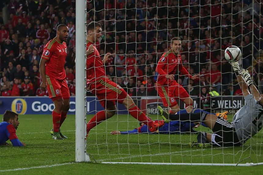 Wales's midfielder Aaron Ramsey (right) watches the ball as he scores past Andorra's goalkeeper Ferran Pol Perez.