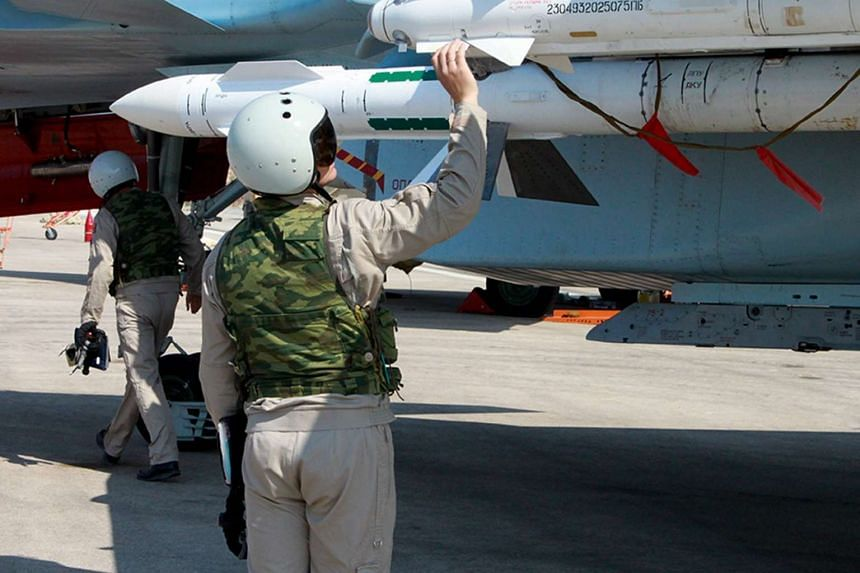 Russian pilots checking the weapons of a Russian warplane at the Syrian Hmeymim airbase, outside Latakia, Syria, on Oct 5, 2015.