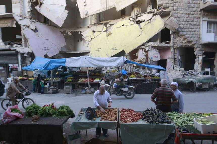 Civilians shop for vegetables and fruits displayed in front of a damaged building in Syria's war divided Aleppo.
