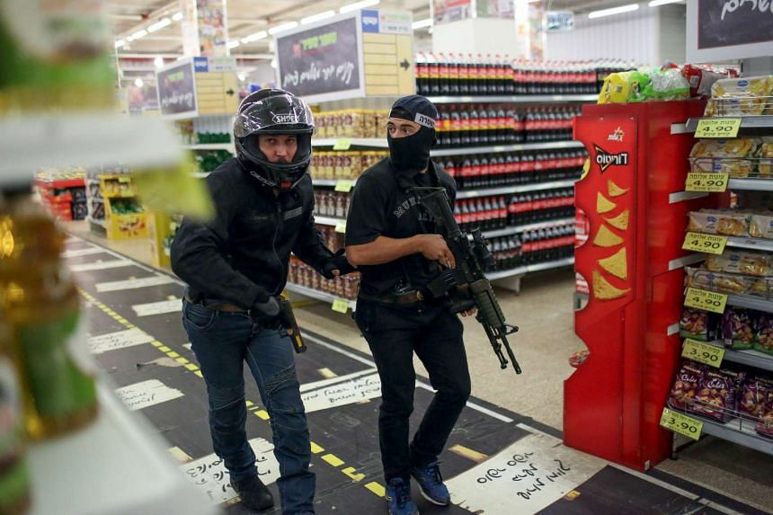 Israeli undercover security personal search a supermarket inside the Central Jerusalem Bus Station after a woman was stabbed by a Palestinian outside the place on Oct 14, 2015.