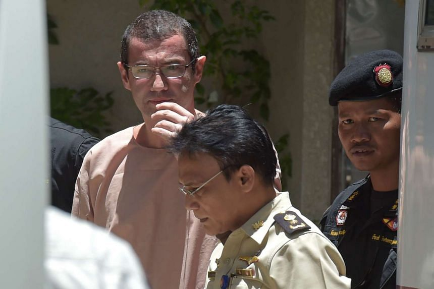 Swiss national Xavier Andre Justo, 49, being escorted by Thai officials as he leaves a courthouse in Bangkok on Aug 17, 2015. The Swiss man was jailed for three years in Thailand on Aug 17 for attempting to blackmail Saudi oil company PetroSaudi Inte