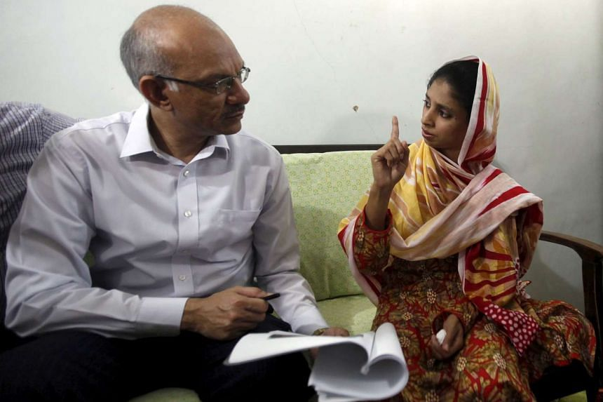 Prabhat K. Jain (left), second secretary at the High Commission of India in Pakistan, shows Geeta, a Hindu deaf-mute woman, pictures of families in India who have claimed to be her parents and siblings, during his visit to the Bilquis Edhi Foundation