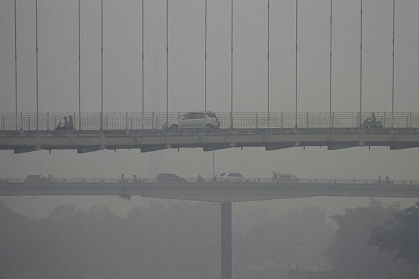 Left: The Siak Bridge in Pekanbaru, Riau, shrouded in haze on Sunday. Fires that cause haze are often started to clear land for farming or to plant oil palm crops.