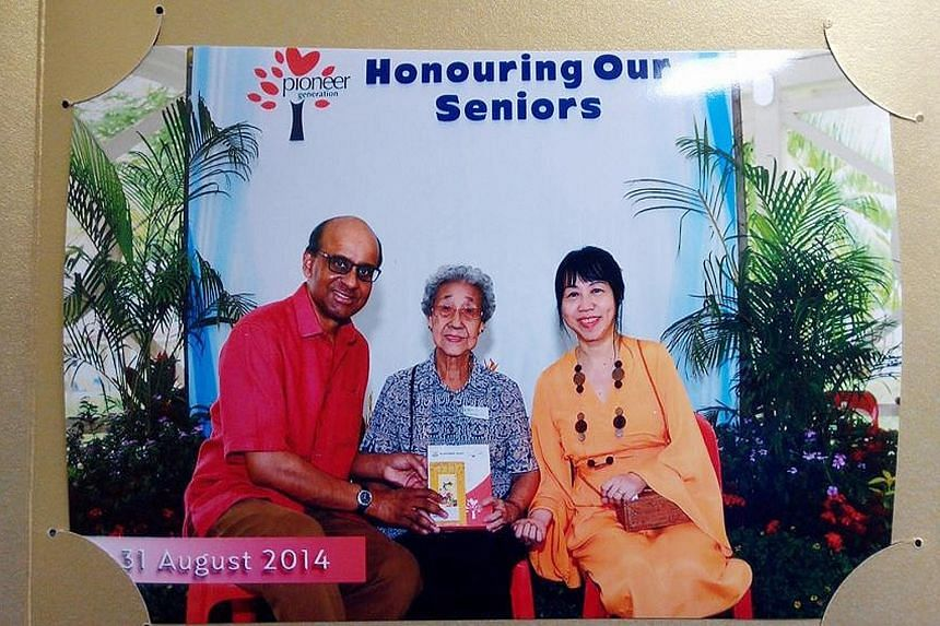 """Madam Khoo Bee Hua (centre) receiving her Pioneer Generation card from Deputy Prime Minister Tharman Shanmugaratnam in August last year. With them is Mrs Tharman. Mr Tharman, who visited Madam Khoo in hospital yesterday, called her the """"archetypal pi"""