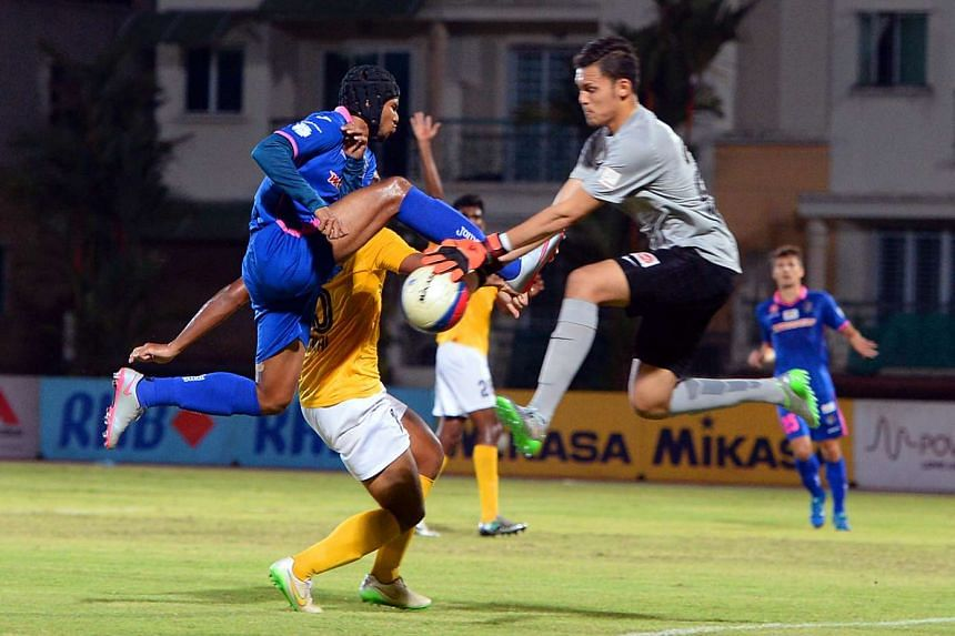Fazrul Nawaz (left, in blue) in action against Harimau Muda's goalkeeper during the S-League match between Warriors FC and Harimau Muda.
