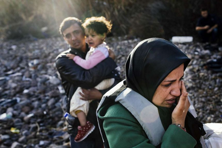 A migrant family arriving at the Greek island of Lesbos, after crossing the Aegean sea from Turkey, on Oct 12.