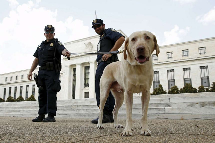 Police officers stand with their dog Brodie outside the Federal Reserve in Washington.