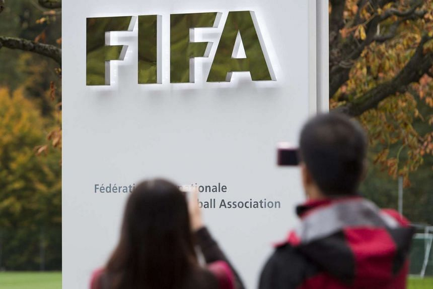 Tourists photograph the Fifa logo at Fifa headquarters in Zurich, Switzerland.