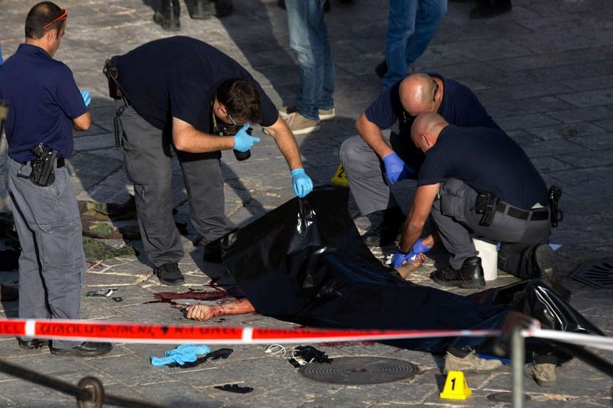 Israeli security forces and forensic police inspect the body of a man who attempted to carry out a knife attack in the Old City, in east Jerusalem.