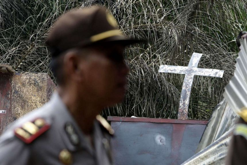 Indonesian security forces inspecting the scene of a burned Church in Aceh Singkil on Oct 14.