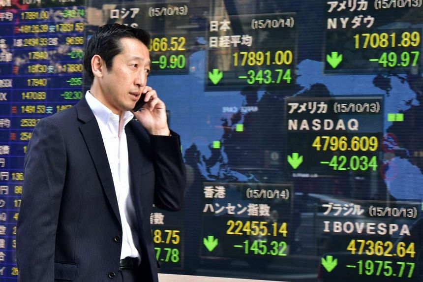 A businessman walks past a share price board in Tokyo on Oct 14.
