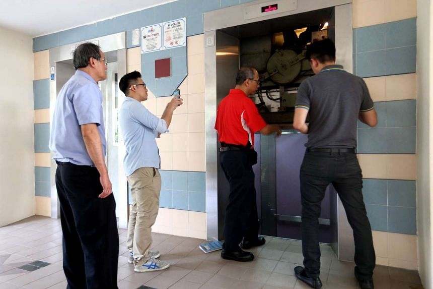 Lift service repairmen inspecting the lift B at block 322 Tah Ching Road.