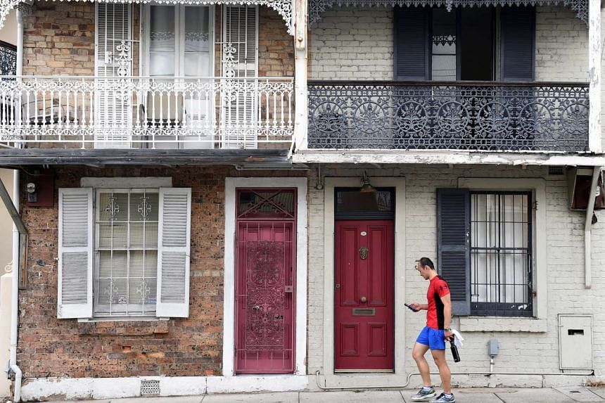 A man walks past residential houses in Sydney, Australia, on Oct 14, 2015.