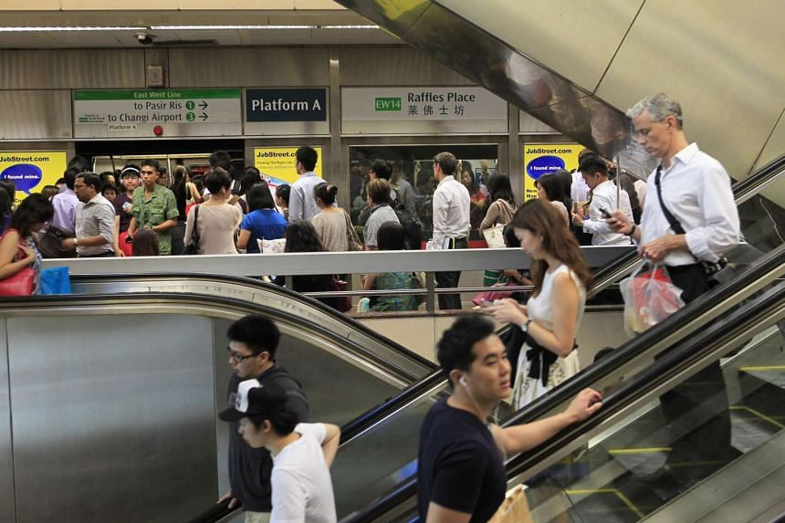 Commuters during the peak hour period at Raffles Place MRT station.