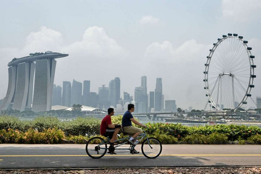 Tandem bicyclists ride their vehicle as the Singapore city skyline is seen shrouded in haze on Oct 9, 2015.