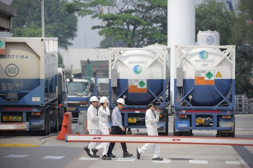 Workers at Leeden National Oxygen at 21 Tanjong Kling Road in the Jurong industrial area yesterday. A fire in a lab at the premises on Monday killed one and injured seven others. Investigations are ongoing.