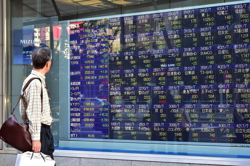 A file picture of a man looking at share prices board in Tokyo. PHOTO: AFP
