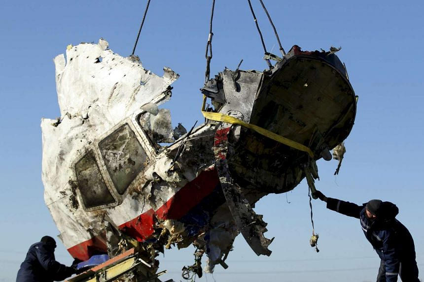 Local workers transport a piece of the Malaysia Airlines flight MH17 wreckage in a 2014 file photo.