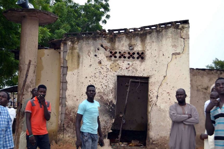 People standing outside a mosque where a suicide bomber killed over 20 worshippers in Maiduguri, on Sept 21.