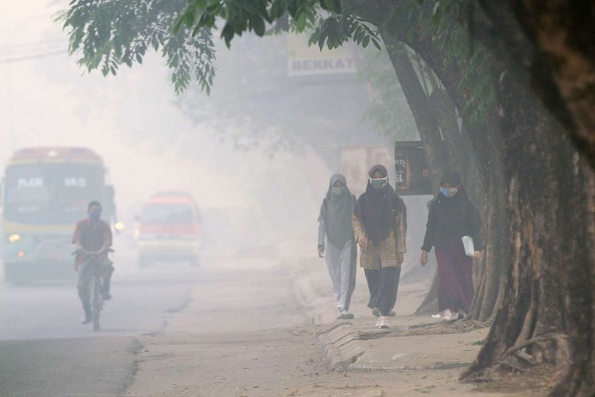 Indonesian pedestrians wearing face masks to protect against air pollution in Palembang on Oct 8.