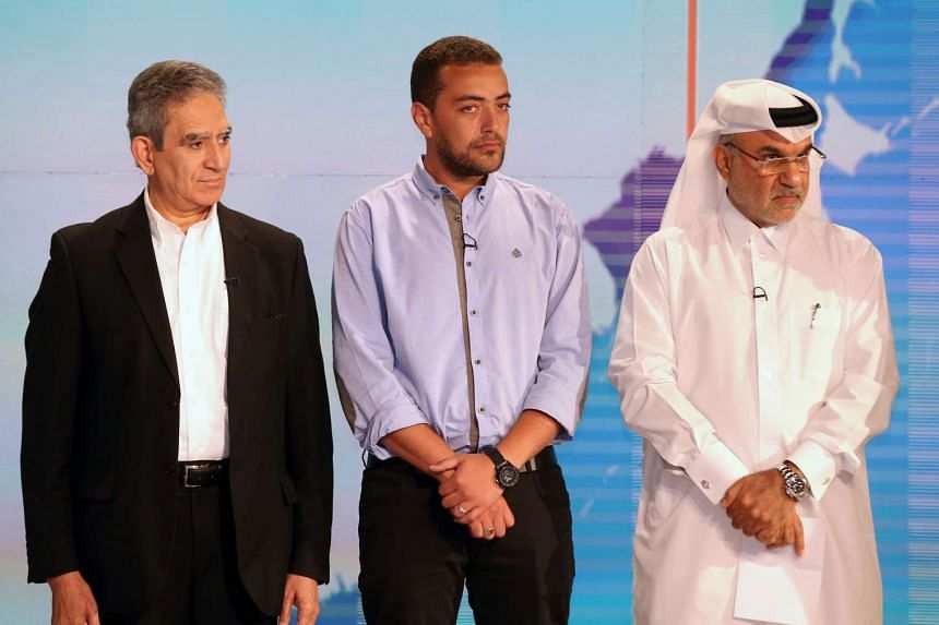 (From left to right) Al-Jazeera Media Network's acting director general, Mostefa Souag, Al-Jazeera English's journalist Baher Mohamed and executive director of global communication, Abdulla al-Najjar, attend a welcome ceremony for its freed journalis