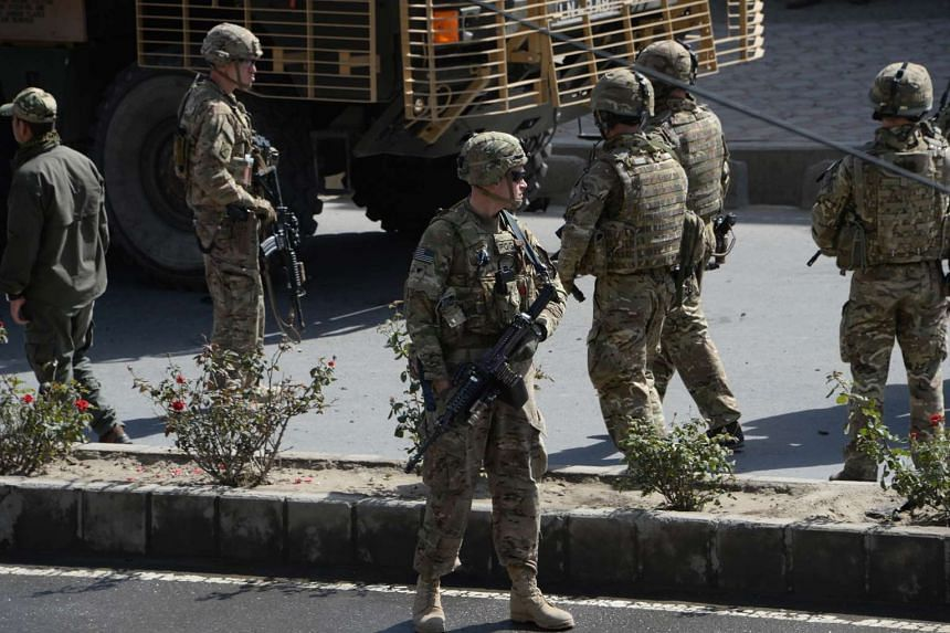 In this photograph taken on Oct 11, 2015, US soldiers arrive at the scene of a suicide car bomb attack that targeted foreign military vehicles at Jo-e-Sher in Kabul. President Barack Obama announced on Oct 15, 2015, that thousands of US troops will r