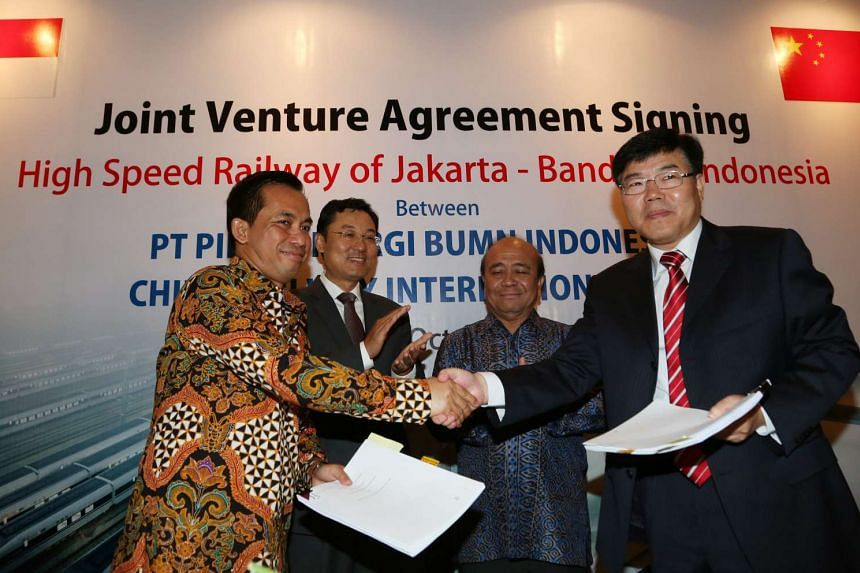 President Director of Indonesian state consortium PT Pilar Sinergi BUMN, Dwi Windarto (left) shakes hands with the Chairman of the Board of China Railway International, Yang Zhong Min (right) during the signing ceremony of the Indonesia-China Joint V
