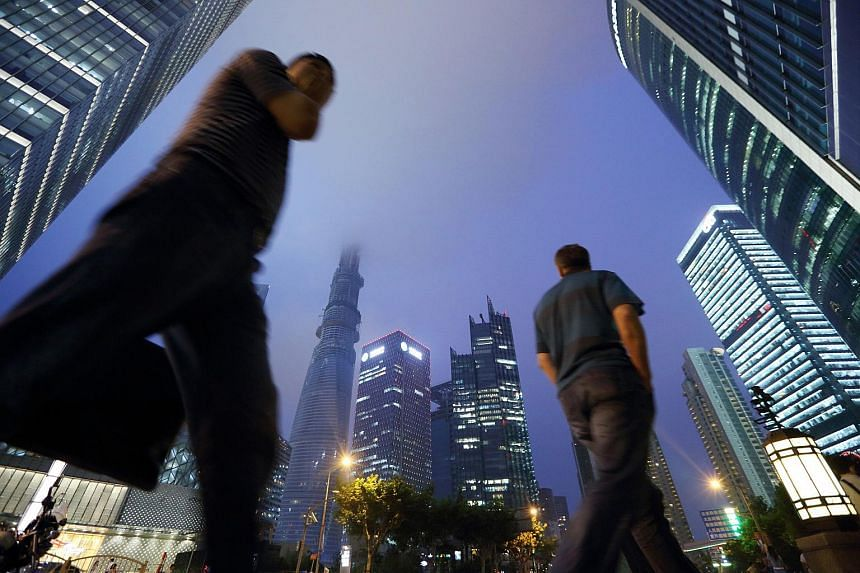 Pedestrians walking past commercial buildings in the Lujiazui district of Shanghai in 2013.