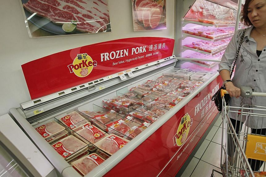 A customer passes by the frozen pork section at an NTUC FairFrice outlet in 2013.