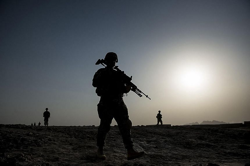 US soldiers on patrol near Kandahar Airfield in Afghanistan in a 2014 photo. US President Barack Obama is giving up on his hopes of bringing nearly all American troops home from Afghanistan by the end of his term in January 2017. The shift in plannin